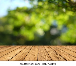 Brown wood surface on a green background. Green leaf background, blurred sun, abstract bokeh can be used for displaying or editing your product.