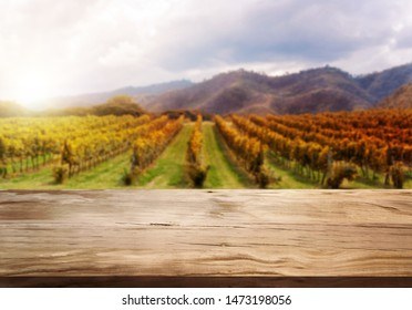 Brown wood table in autumn vineyard landscape with empty copy space on the table for product display mockup. Winery and wine tasting concept.