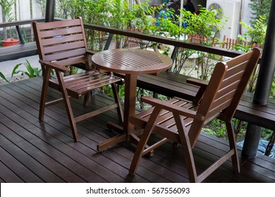 brown wood table and chairs set on terrace.