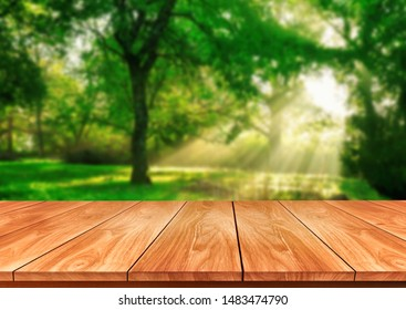 Brown wood table in green blur nature background of trees and grass in the park with empty copy space on the table for product display mockup. Fresh spring and natural product concept.