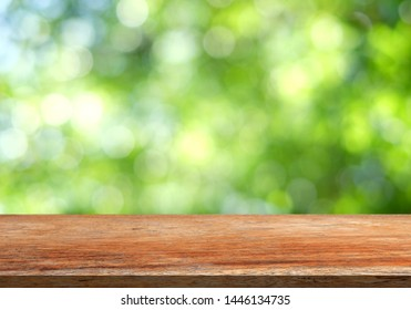 Brown wood table top on a green blur abstract background Bokeh background Blurred green leaves  Design and product concept.