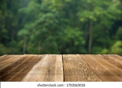 Brauner Holztisch auf grünem, abstraktem Hintergrund Bokeh-Hintergrund Unscharfe grüne Blätter Design und Produktkonzept.