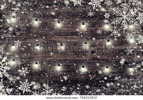 The brown wood texture with garland and snow flakes over it. Christmas holiday background