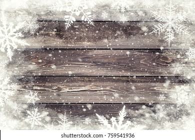 The brown wood texture with snow flakes over it. Winter background