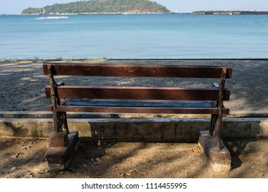 The brown wooden bench fixed on the concrete ground at the seaside