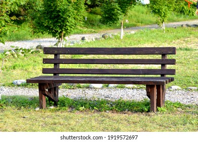 Brown wooden bench in the park. Summer sunny day. Green grass and trees. Resting and relaxing area. Empty bench for sitting. Wood exterior material