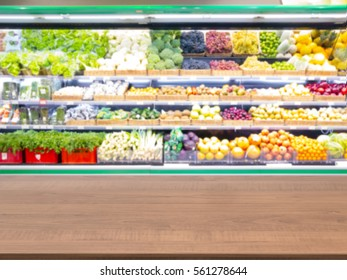 Brown wooden board empty table in front of blurred background. Perspective dark wood table over blur in supermarket fruits and vegetables shelf. Mock up for display or montage your product.