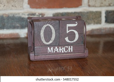 Brown Wooden Calendar Showing the Date of March 5th with Brick Background