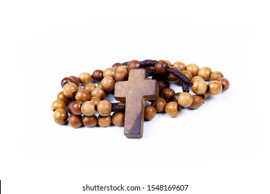 Brown wooden christian rosary curled up, christianity religious symbols isolated on white. Cross symbol in the middle. Chaplet of Divine Mercy prayer conept. Faith, belief. Studio shot