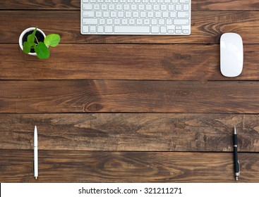 Brown Wooden Desk with Stationery and Electronics Natural Wood Background Small Green Plant Computer Mouse and Keyboard Black and White Pens Top View