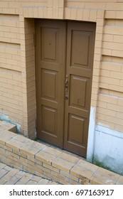 Brown wooden door to the basement. Architecture