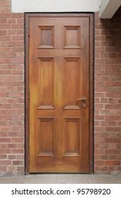 Brown wooden door on brick wall