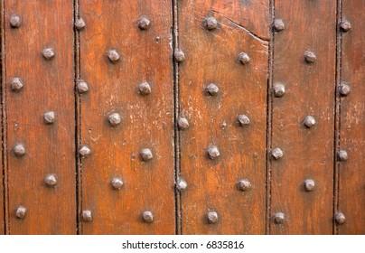 Brown wooden door panel with metal stud pattern