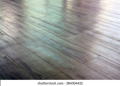 Brown wooden floor with light reflection.