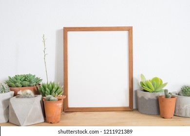 Brown wooden frame poster with cactus and succulents in pot on table