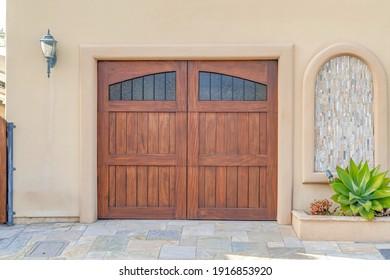 Brown wooden garage door with glass panes in Huntington Beach California