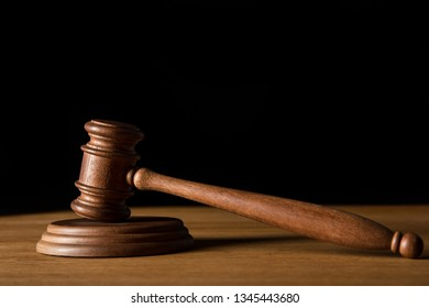 brown wooden gavel on table isolated on black with copy space