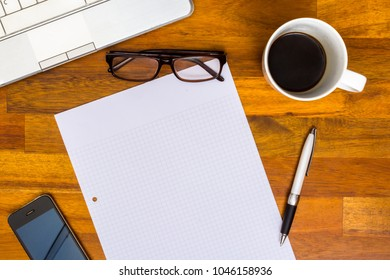 brown wooden orking desk with laptop, college block note paper, Pen, Mobile Phone, Glasses, Black Coffee