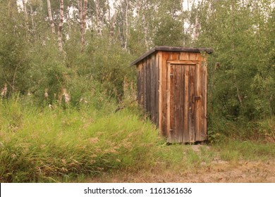 A brown wooden outhouse surrounded by green grass, shrubs and trees.