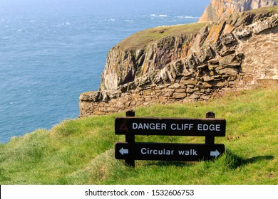 Brown Wooden sign board  Warning of  Cliff Edge  and directing circular route