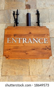 """Brown wooden sign """"Entrance"""" on the stone wall."""