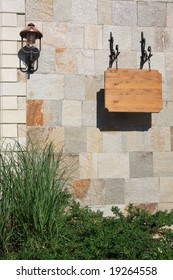 """Brown wooden sign """"SPA"""" on the stone wall."""