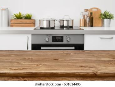 Brown wooden table on defocused pastel color kitchen interior background