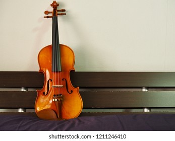 Brown wooden violin resting on a wooden bed head