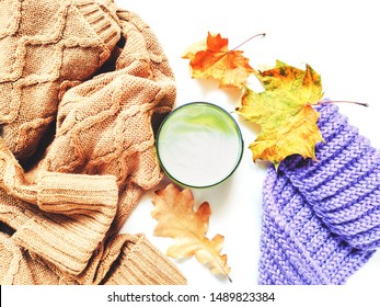 Brown wool sweater, knitted purple scarf, dry yellow leaves and a jar of moisturizer. Natural cosmetics for face and body skin care in autumn and winter