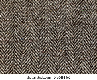 Brown woolen fabric striped zigzag. Herringbone tweed, Wool Background Texture. Coat close-up. Expensive men's suit fabric. High resolution