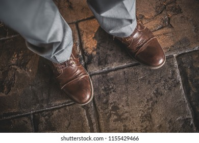 Brown worn out dress shoes paired with grey pants.