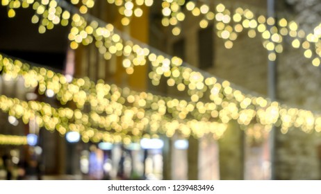 brown yellow and red flickering Christmas lights. bokeh blurred out of focus background at night. decorated city street