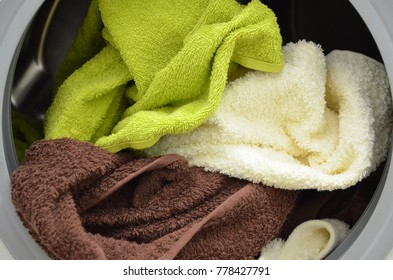 Brown, yellow, white towels in an open washing machine