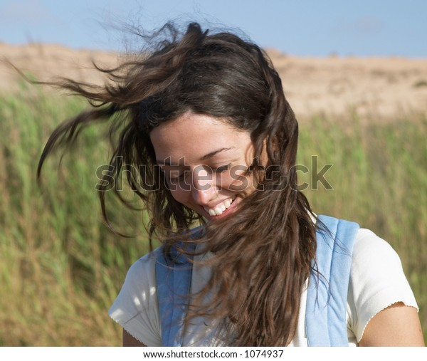 Brown young caucasian female, long hair, outdoor with wind and sun, Portugal