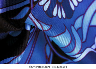 brown-blue fabric with a print of white flowers, geometric lines. Texture, background, pattern
