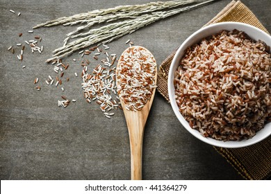Brown/Coarse Rice on wooden spoon with boiled rice. Selective focus.