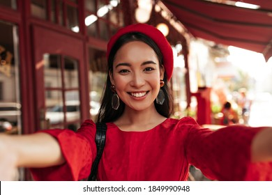 Brown-eyed brunette Asian woman in red dress, bright beret and with stylish earrings smiles widely and takes selfie in street cafe.