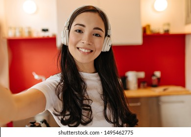 Brown-eyed woman in white headphones smiles and takes selfie in kitchen