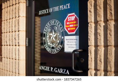 BROWNFIELD, TX - 10/09/2020 - Door entrance to Angie p. Garza Justice of Peace in Brownfield, Texas, Terry County with the seal of the State on the glass