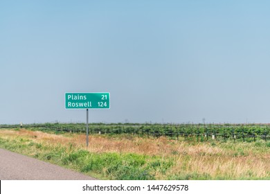 Brownfield, USA Texas countryside industrial town sign for Plains and Roswell New Mexico miles on road direction view from 380 highway