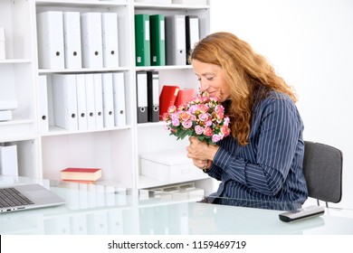 brown-haired  businesswoman in the office with big bouquet of flowers