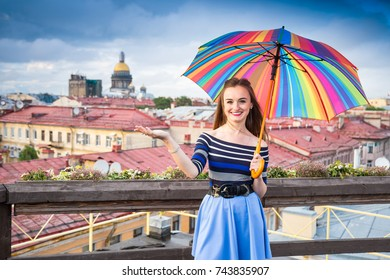 brown-haired white-teeth smiling girl wearing blue skirt and blouse with open bright umbrella stands on the roof of the building