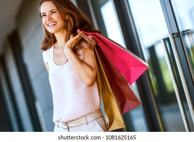 A brown-haired woman holding three shopping bags - gold, brown, and red - over her left shoulder laughs and smiles as she looks out into the distance.