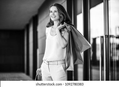 A brown-haired woman holding three shopping bags - gold, brown, and - over her left shoulder laughs and smiles as she looks out into the distance. She is relaxed, happy, and effortlessly stylish