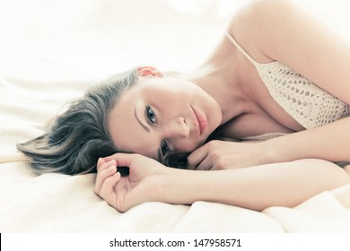 brown-haired woman lying on her duvet in her bedroom