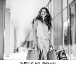 A brown-haired woman wearing muted, gentle shades holds five colourful, patterned shopping bags during a successful shopping spree. Walking outside, she is enjoying the warmth of a summer day.