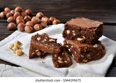 Brownie cake with chocolate and hazelnuts with some hazelnuts close