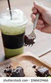 Brownie with green tea drink on the fork cut in piece and ready to eat. dessert for afternoon tea.