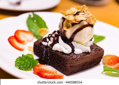 Brownie on white plate with vanilla ice cream and stawberry