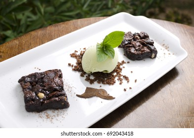 Brownie pie with pistachio ice cream on a white plate